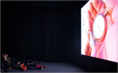 """""""The Clock,"""" a video work by Christian Marclay, uses thousands of film and television clips of timepieces to create, minute by minute, a 24-hour montage that unfolds in real time."""